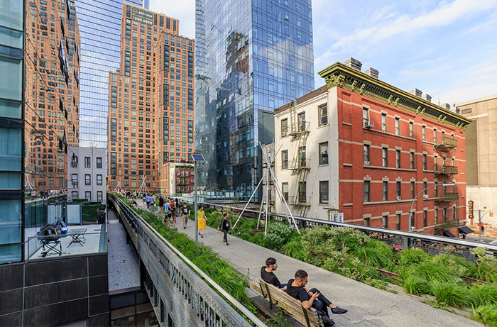People walking on the high line with heritage buildings in the back