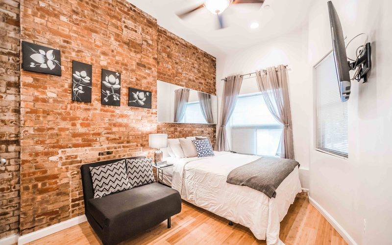 Room with brick wall, window and bed